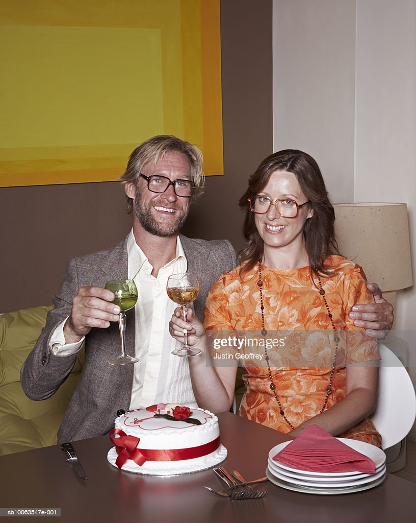 Couple wearing spectacles raising glasses, smiling, portrait : Stock Photo