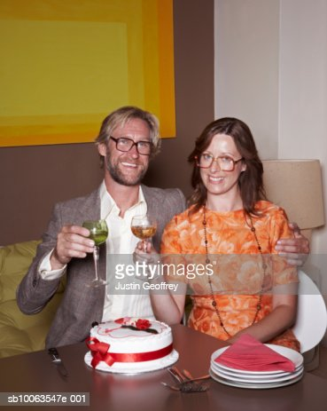 Couple wearing spectacles raising glasses, smiling, portrait : Stock Photo