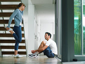 Couple wearing sports clothes in house, woman performing leg stretch