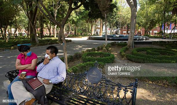 A couple wearing surgical masks sit on a bench at an empty park In Mexico City on April 28 2009 The swine flu virus that has killed dozens in Mexico...