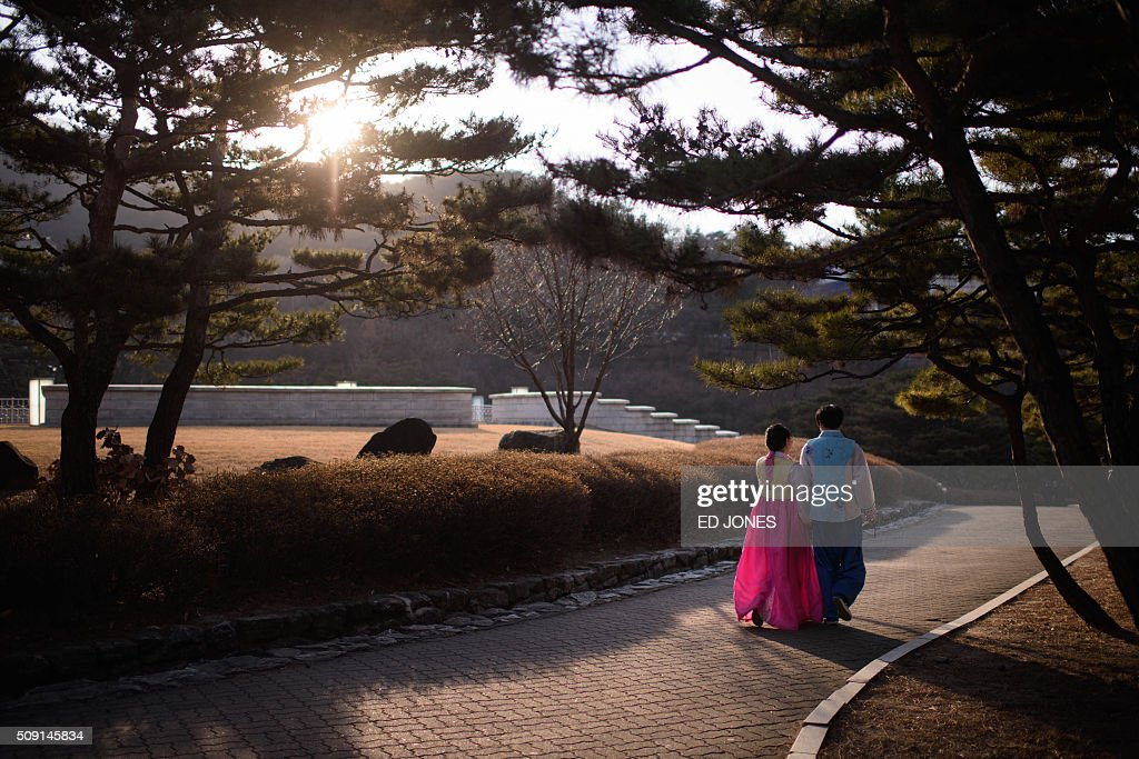A couple wearing traditional Korean 'hanbok' walk in a park in Seoul on February 9, 2016. South Korea is marking the Lunar New Year. AFP PHOTO / Ed Jones / AFP / ED JONES