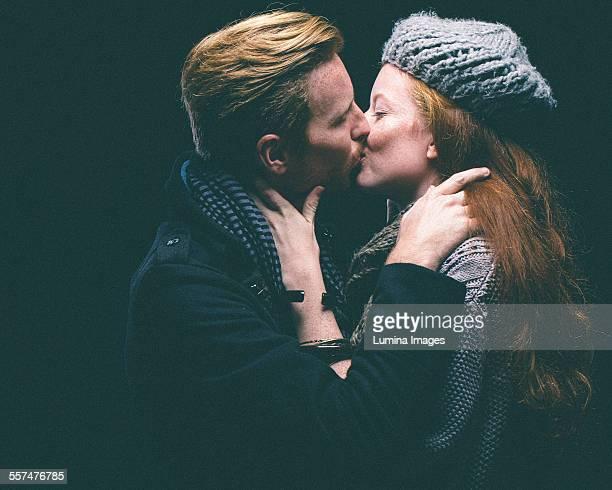 Couple wearing warm clothing kissing