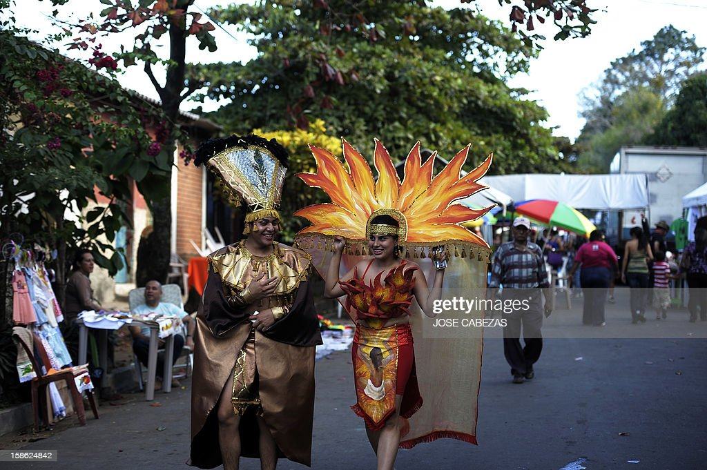 A couple wears traditional Mayan costumes at Tazumal Archeological site in the town of Chalchuapa, 70 km west of San Salvador, El Salvador on December 21, 2012 during a ceremony to celebrate the end of the Mayan cycle known as Bak'tun 13 and the start of the Maya new age. AFP PHOTO/ Jose CABEZAS