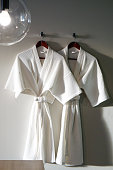 Couple White bathrobe in wooden wardrobe with warm lighting of luxury hotel.