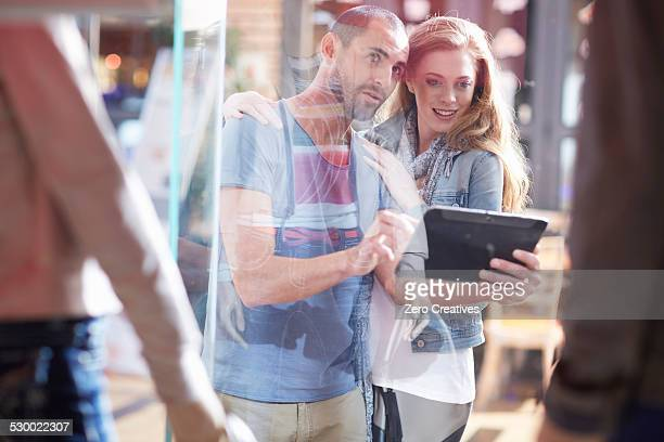 couple window shopping, holding digital tablet