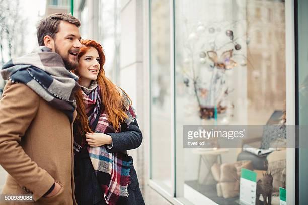 Casal de janela de compras ao ar livre no Inverno cidade rua.