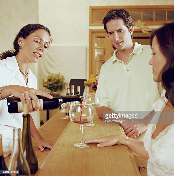 Couple wine tasting, bartender pouring wine into glass