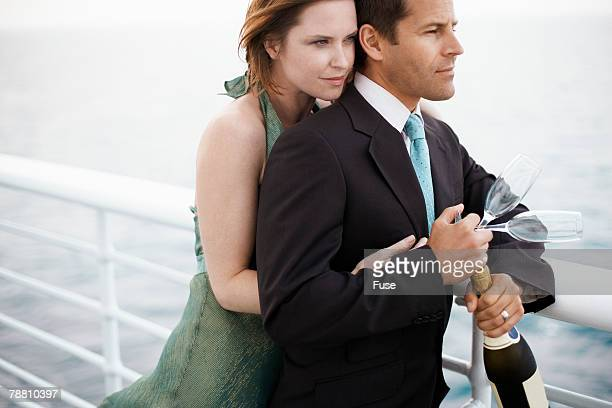Couple with a Bottle of Champagne on Ship's Deck