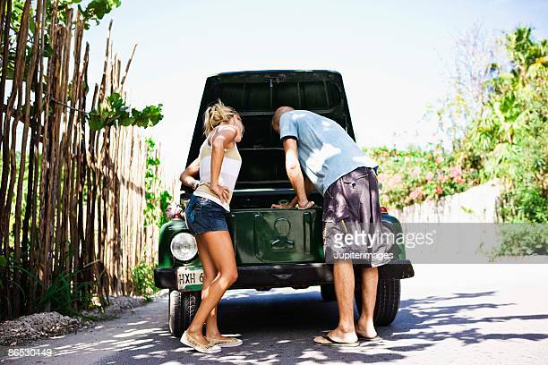 Couple with a broken down car