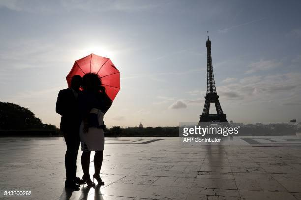A couple with a red umbrella stand at sunrise on the Human Rights square in front of the Eiffel tower on September 6 in Paris / AFP PHOTO / LUDOVIC...