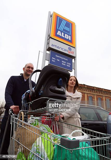 A couple with a small baby take their shopping to their car in the Aldi carpark in Worcester central England on March 23 2015 The struggling middle...