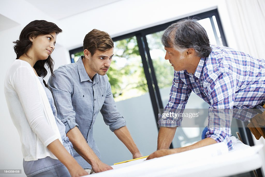 Couple with architect discussing home plan : Stock Photo