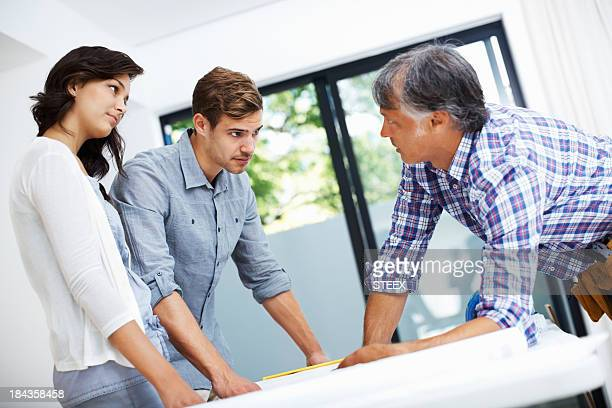 Couple with architect discussing home plan