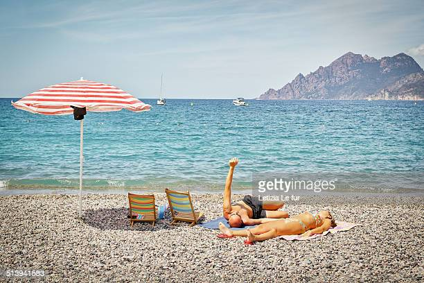Couple with arm in the air with parasol on Porto' s beach in Corsica France