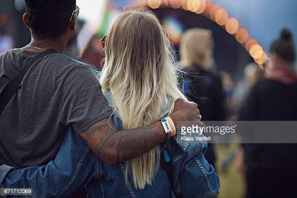 Couple with arms around each other at concert