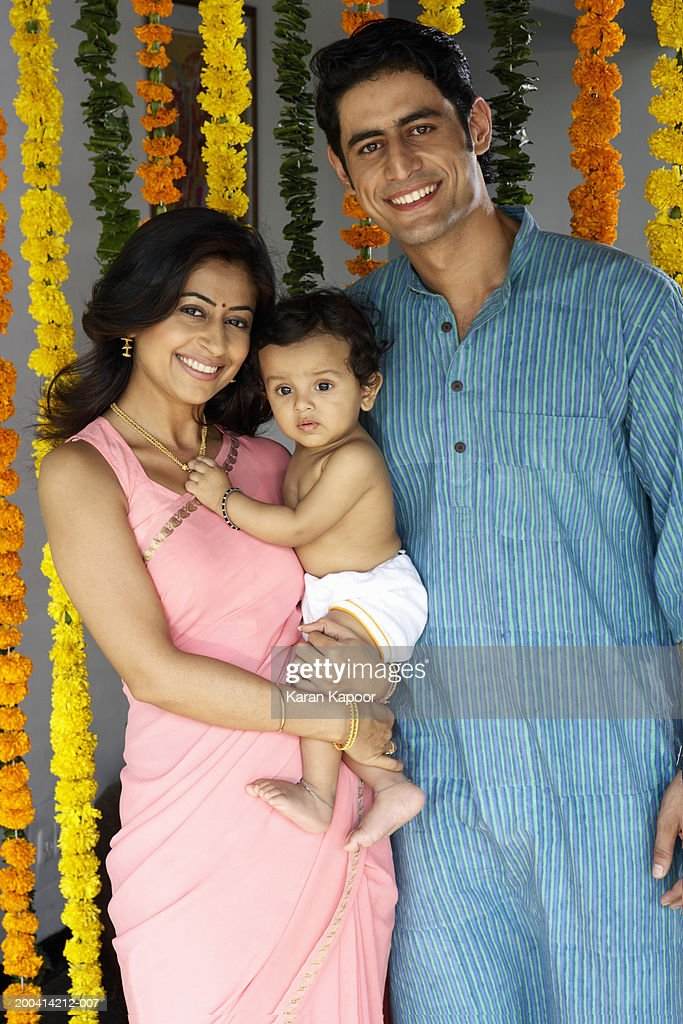 Couple with baby daughter (10-12 months) smiling, portrait : Stock Photo