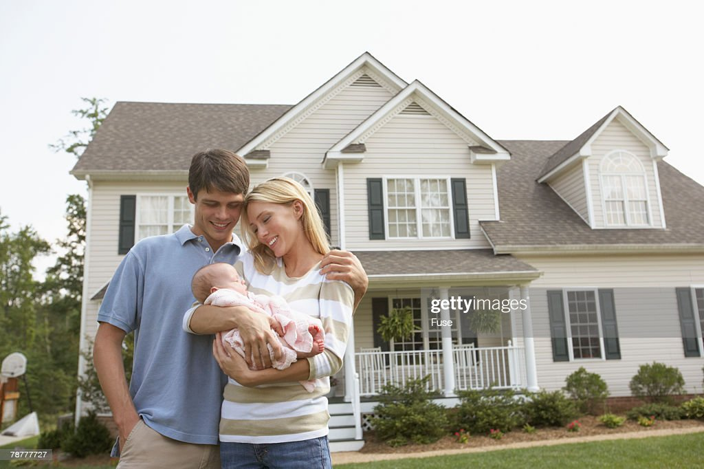 Couple with Baby in Front of Home