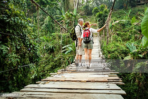 Couple with backpack hiking in rainforest