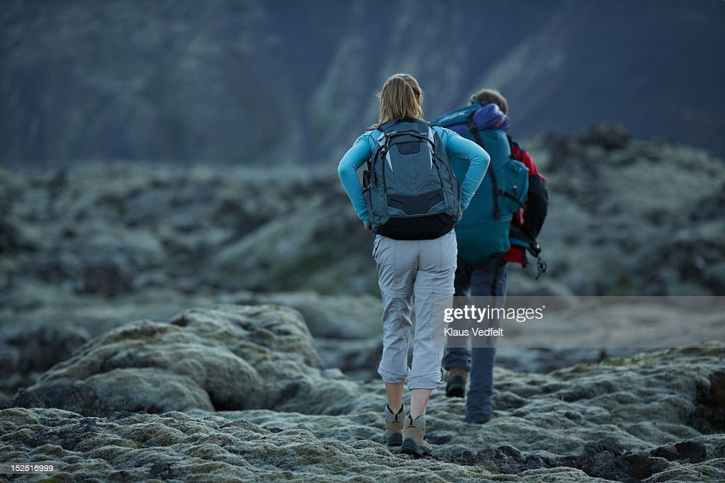 Couple with backpacks walking threw rock landscape : Stock Photo