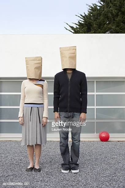 Couple with bags over heads standing in front of garage