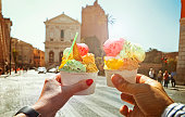Couple with beautiful bright  sweet Italian ice-cream with different flavors  in the hands   on the square in Rome , Italy