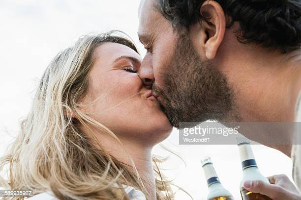 Couple with beer bottles kissing outdoors