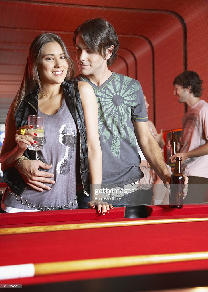 Couple with beverages standing by pool table smiling : Stock Photo