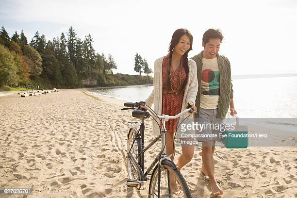 Couple with bicycle on beach