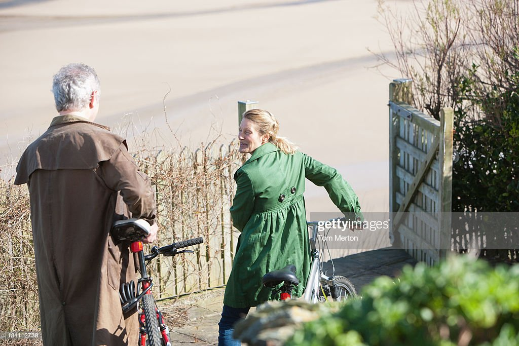 A couple with bicycle outdoors at beach : Stock Photo
