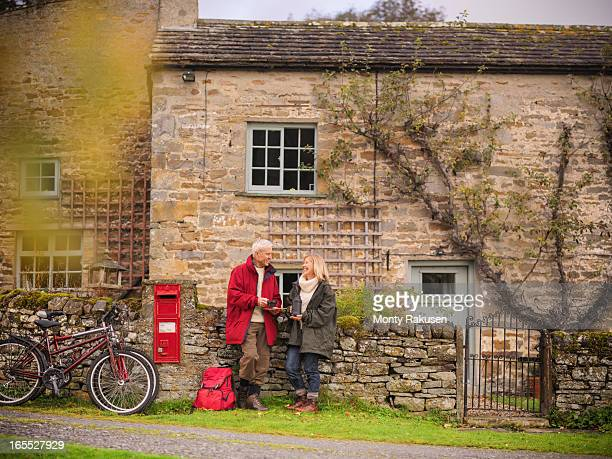 Couple with bicycles standing by dry stone wall and cottage in rural village