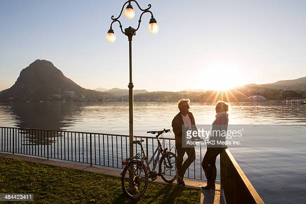 Couple with bikes have conversation by lake edge