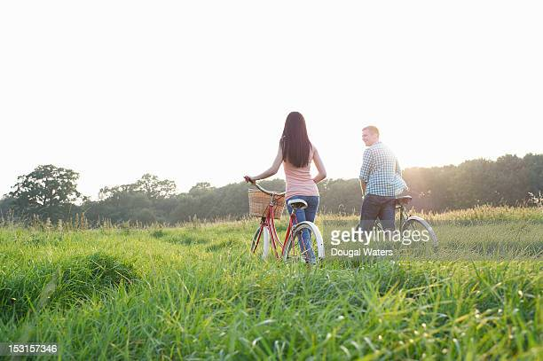 Couple with bikes walking through Summer meadow.