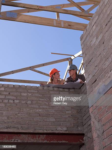 Couple with blueprints at new construction site