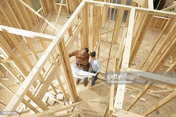 Couple with blueprints standing in building framework