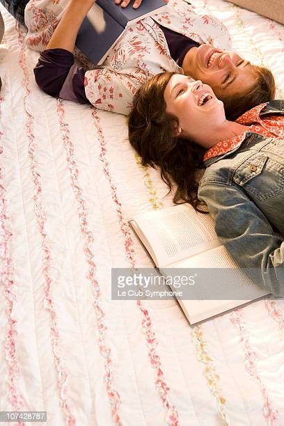 Couple with books laying on bed