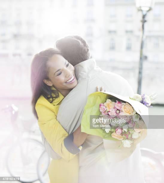 Couple with bouquet of flowers hugging along Seine River, Paris, France