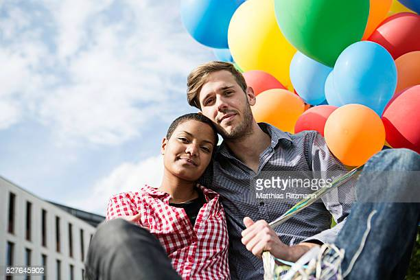 Couple with bunch of colorful balloons in urban scene