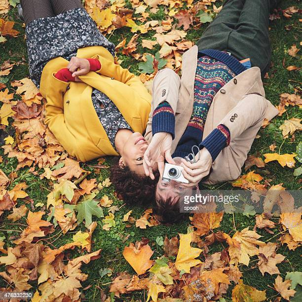 Couple with camera laying on lawn covered with yellow leaves.