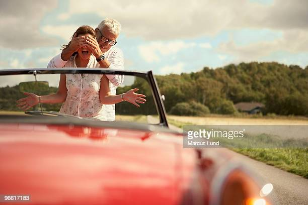 Couple with car, his hands over his eyes