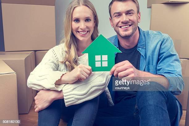 Coppia con scatole di cartone in movimento e casa simbolo