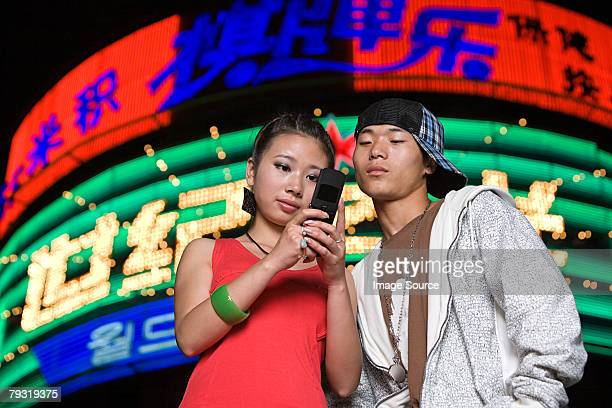 Couple with cellphone by neon light