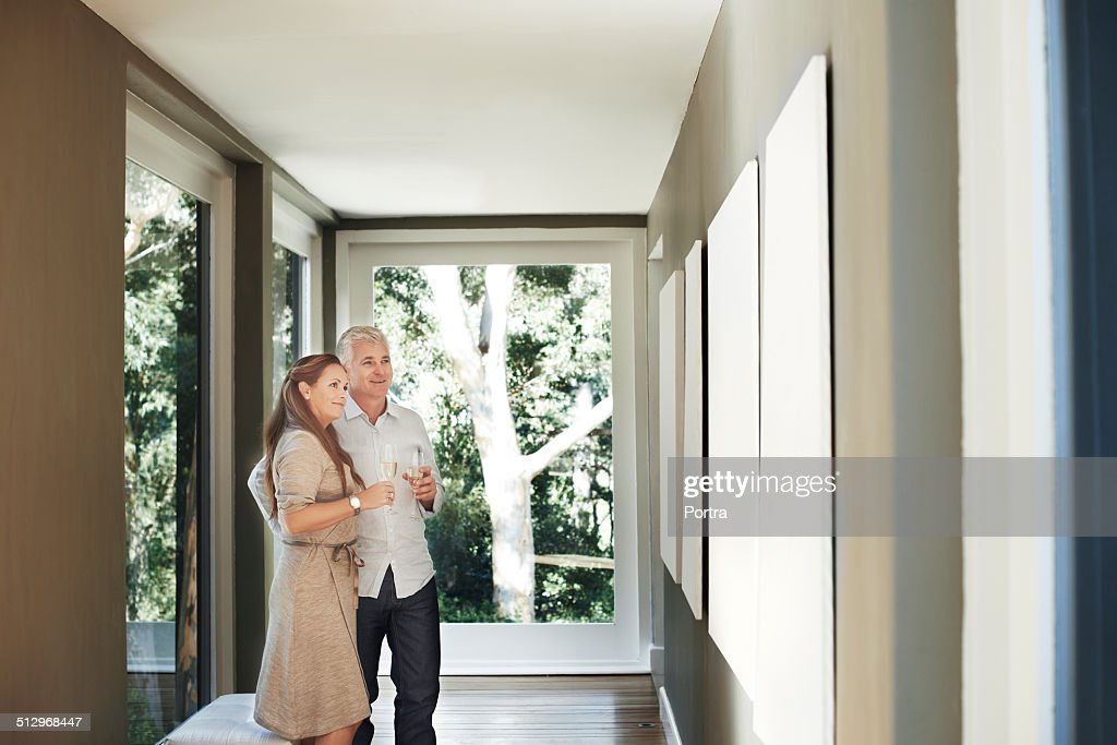 Couple with champagne flutes looking at pictures