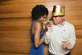 Couple with champagne, man wearing Happy New Year hat and blowing noise maker