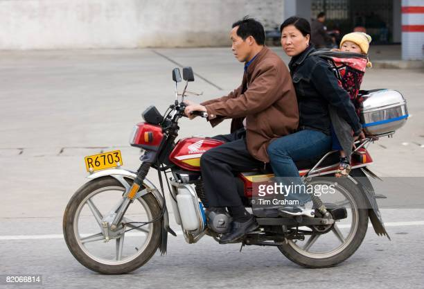 Couple with child on motorbike in Guilin China China has a one child family planning policy to reduce population