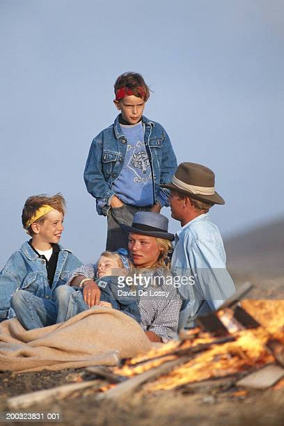 Couple with children (6-11) near campfire