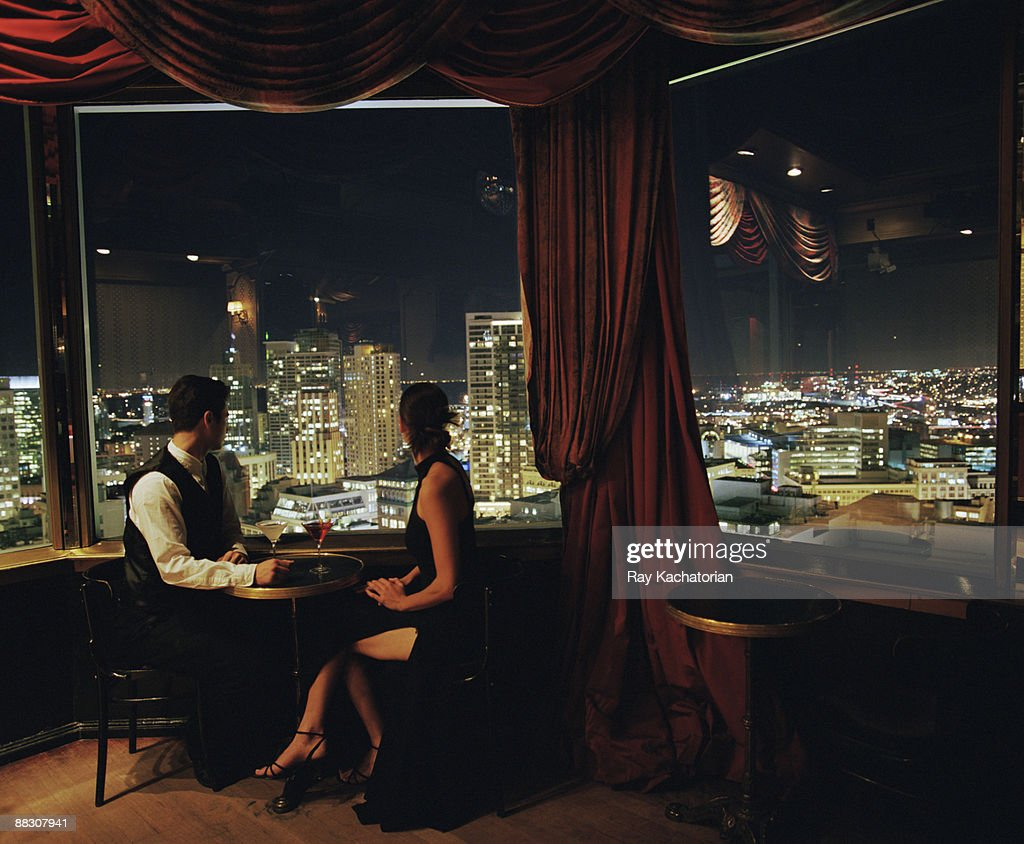 Couple with cocktails overlooking cityscape : Stock Photo