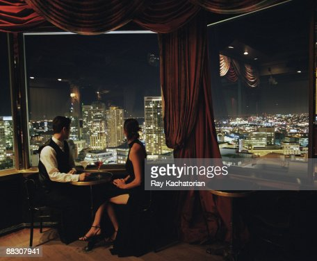 Couple with cocktails overlooking cityscape : Stockfoto