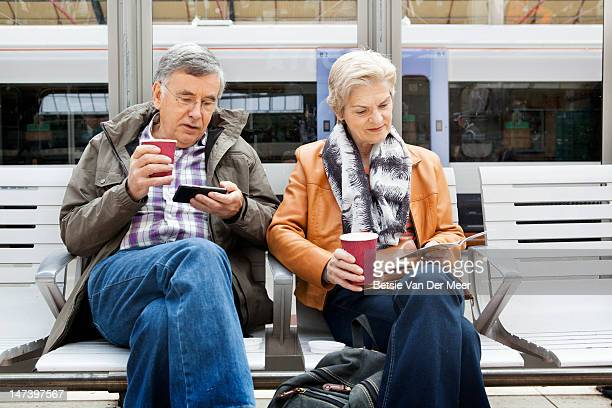 Couple with coffees waiting for train.
