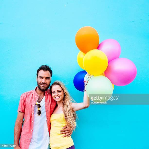 Casal com balões coloridos fundo azul