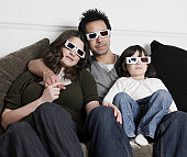 Couple with daughter (2-3 years) watching television with 3-D glasses